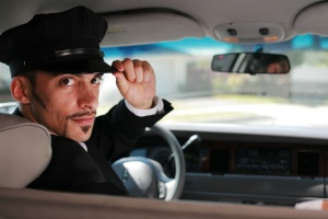 Portrait of a handsome male chauffeur sitting in a car saluting a passanger